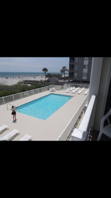 Beautiful ocean view pool with grilling area and tables.