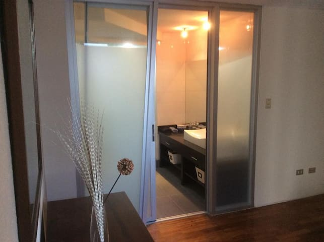 Puerta corrediza de vidrio entre el baño y la habitación.