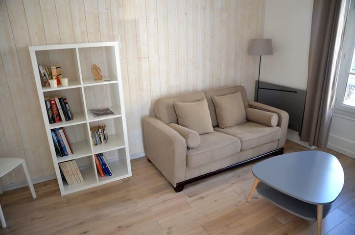 Le salon parqueté, avec le canapé, le convertible et la table base
