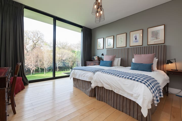 Bedroom 2 has a King sized bed and looks onto a garden full of trees.