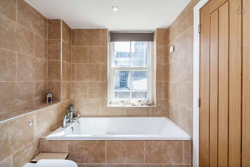 Stylish, modern wet room shared between bedroom one and two. Includes shower, bath and sink.