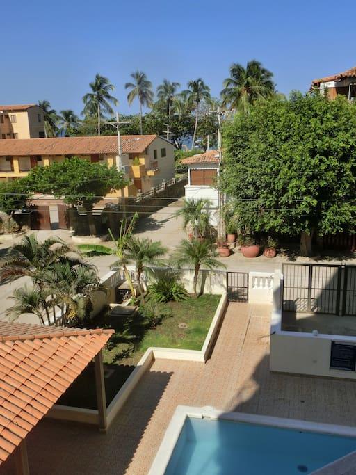 Balcony view towards the beach with the building's pool in the bottom of the picture.  Vista desde el balcón hacia la playa con la piscina del edificio en la parte de abajo.