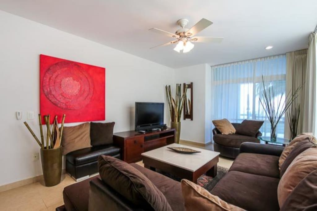 Living room has a comfortable couch, cable TV, and direct access to the ocean