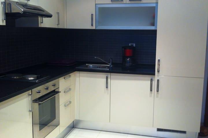 Cuisine bien équipée avec frigo, machine à laver, four, cafétière, assiettes, couverts, verres, ...