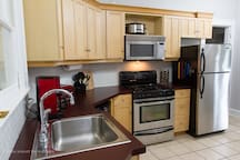 The kitchen features appliances such as a coffee maker, oven, stove, dishwasher, microwave, and crock pot.