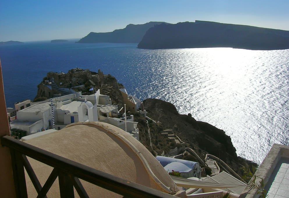 Looking to the left from the balcony,  Kastro ruin at Oia's tip and Thirasia Island across the caldera.