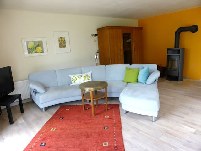 Living area of the ground level apartment with wood fire stove
