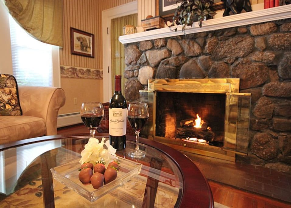 Roosevelt Luxury Suite - sitting room, stone fireplace surround, wine and chocolate covered strawberries