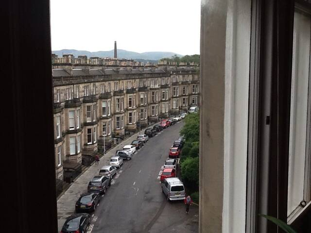 Hi this is a view from the sitting room with the Pentland Hills in the background. They get snow capped sometimes in the winter and you can go walking there.