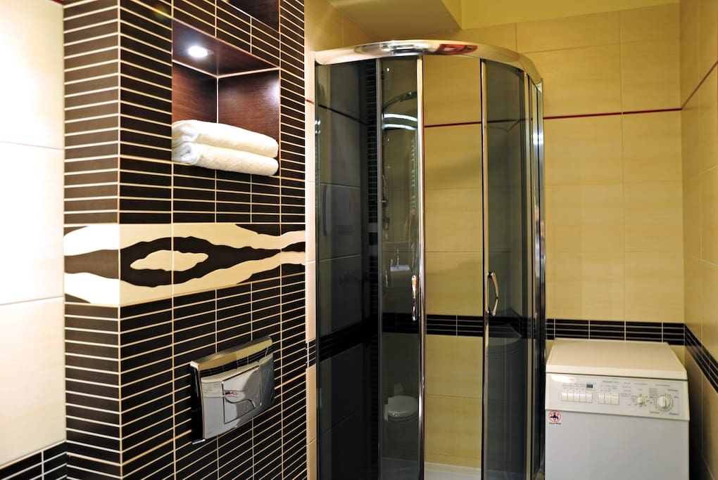 Łazienka z prysznicem, pralką, ręcznikami, suszarką