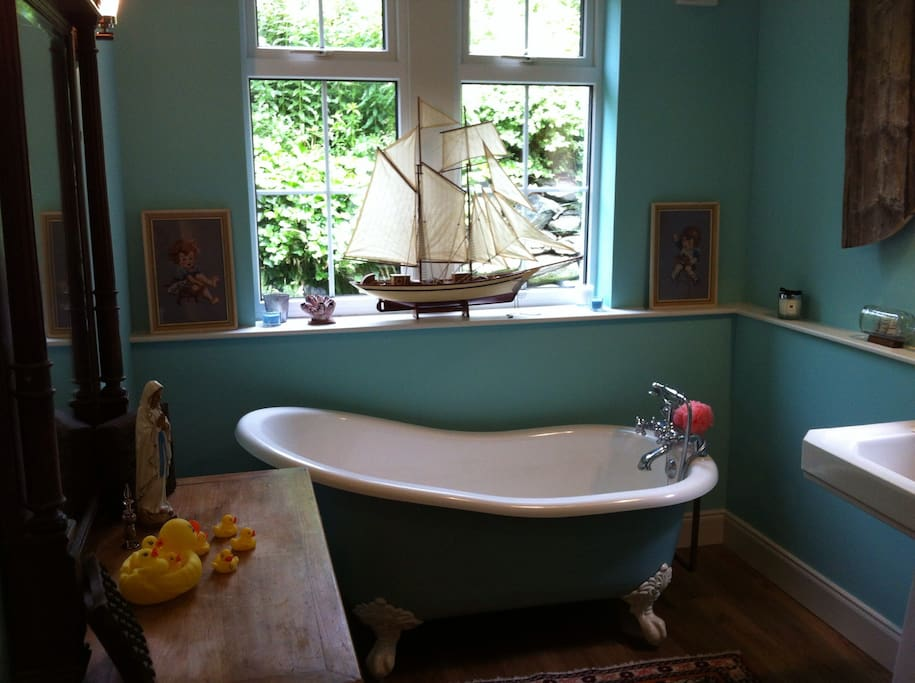 Roll top bath made from volcanic stone, with large antique french mirror and model boat in the downstairs bathroom