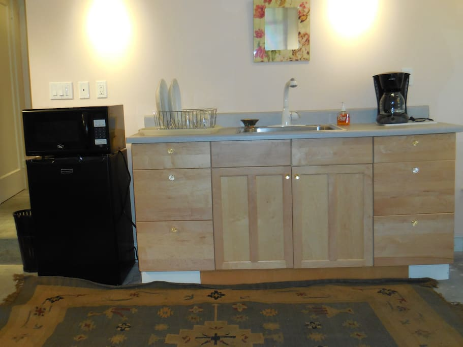 Kitchenette, with microwave, refrigerator, and coffee maker.
