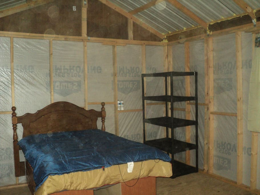Inside view of full size bed and extra storage in Bambi cabin