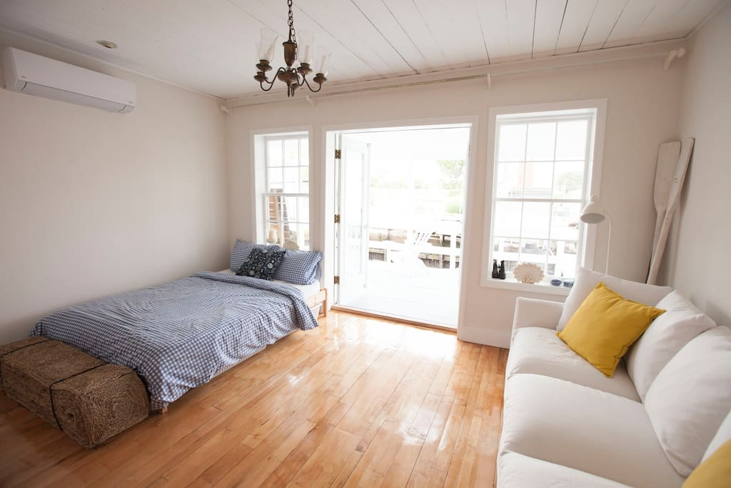 Living room/ bedroom with a  water view. Maple floor handmade by former owner & artisan from local trees. The porch is steps away.