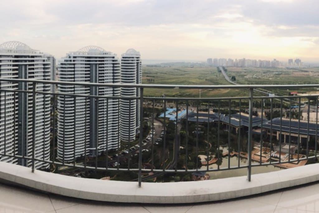 雨过天晴拍阳台,110平米大的阳台呈半圆形状环绕客厅,可以俯瞰整个小区景观和海岸线以及远处群山。