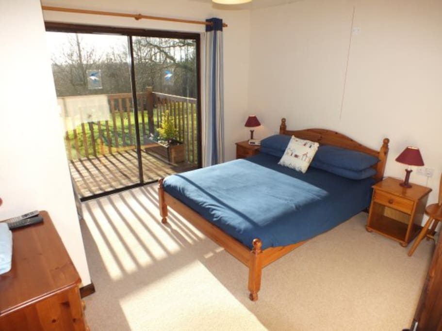 The master bedroom in Swallow lodge has a fitted double wardrobe, dressing chest, HD TV and wide patio doors to the balcony which overlooks the lake