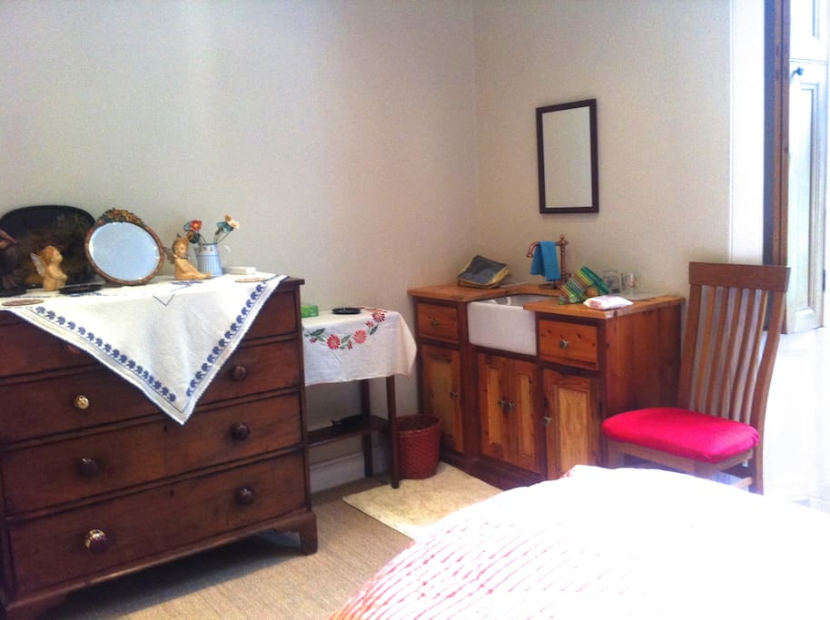 The bedroom has a wash-hand basin and plenty of storage