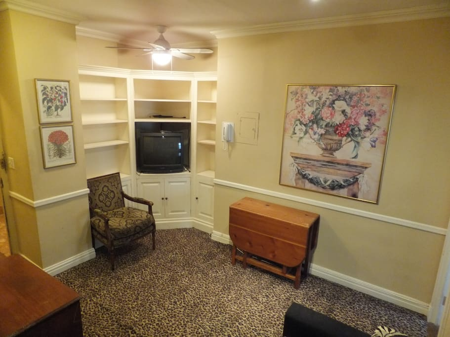 Sitting room has microwave, toaster, coffee maker, mini-fridge, folding-leaf dining table, 2 arm chairs, 2 folding TV tables, cabinets/shelves and large closet.