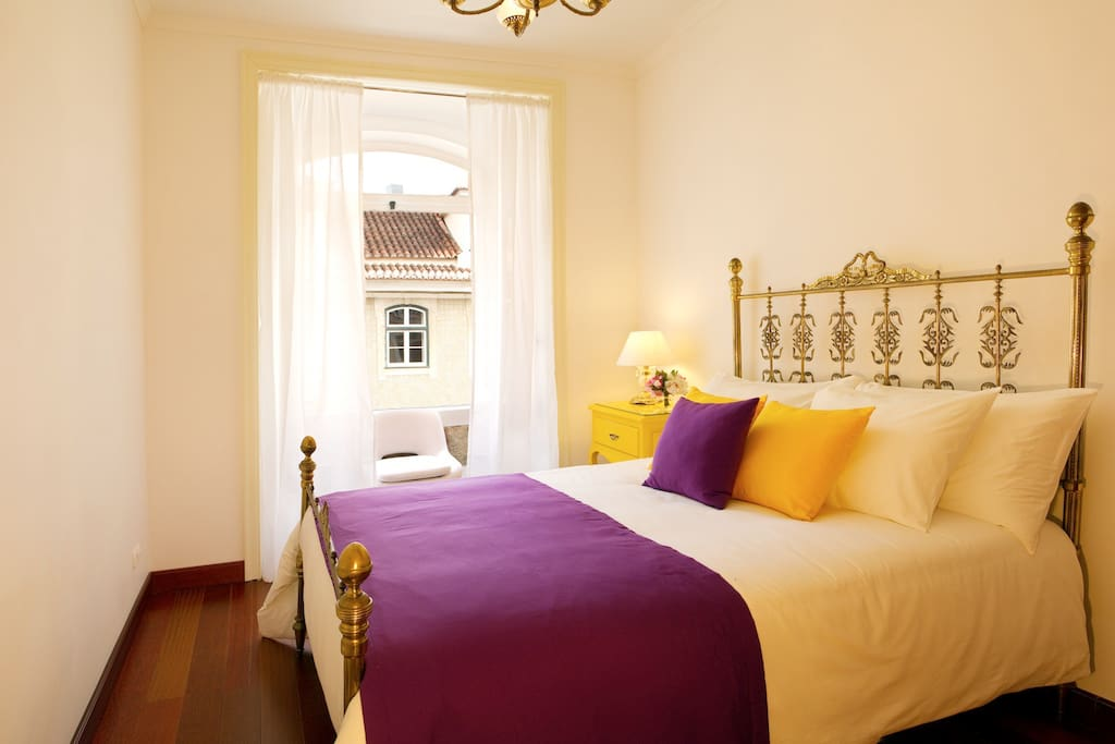 Bedroom with an antique double bed, equipped with a spacious wardrobe