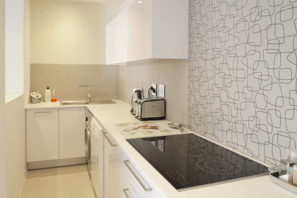 Ultra modern and fully fitted open plan kitchen with Smeg dishwasher and Samsung washing machine.