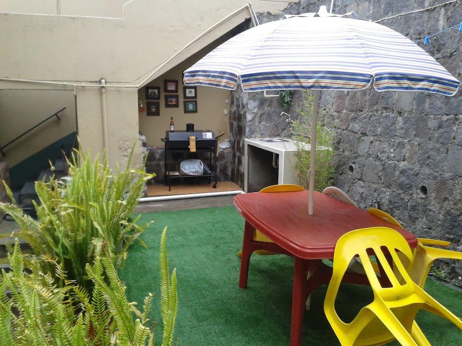 Zona B.B.Q. con asador, fregadero y mesas con sillas y parasol.