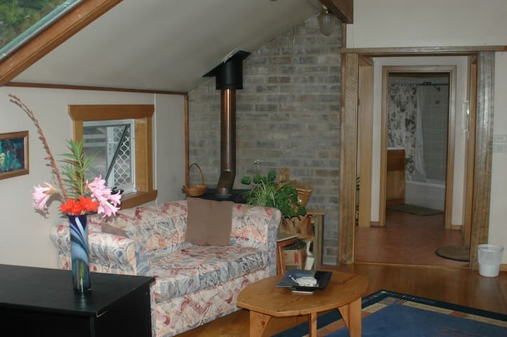 View of the sitting area with wood-burning stove and bathroom in the distance.