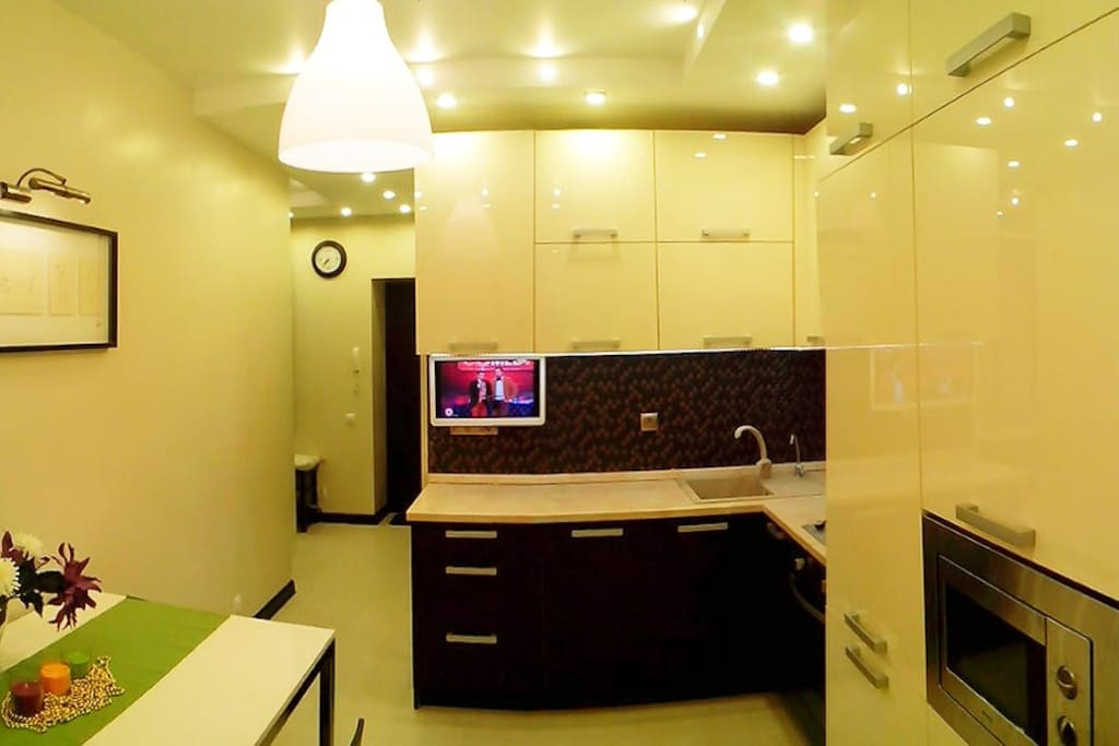 Kitchen with TV, fridge, microwave, gas stove and oven, electric kettle and drink water filtering system.