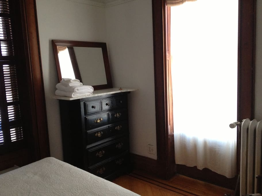 The room has a double bed, two sunny windows, a heater, a dresser and mirror and a place to hang clothes.