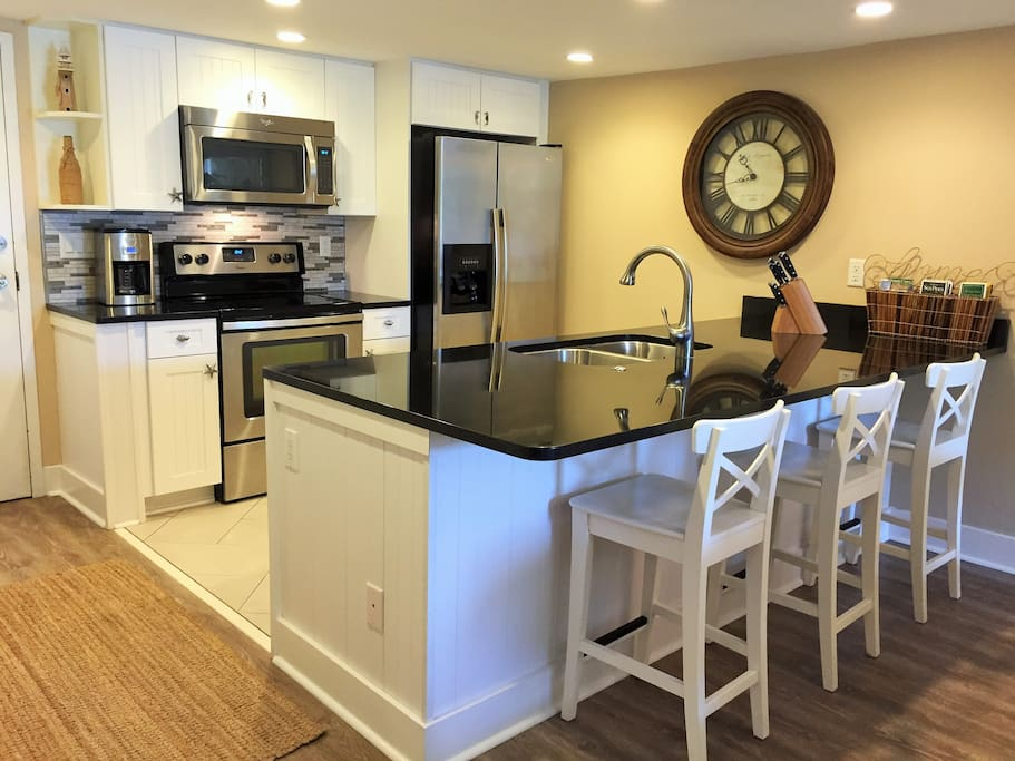 Brand-new kitchen and appliances with large granite bar and three bar stools