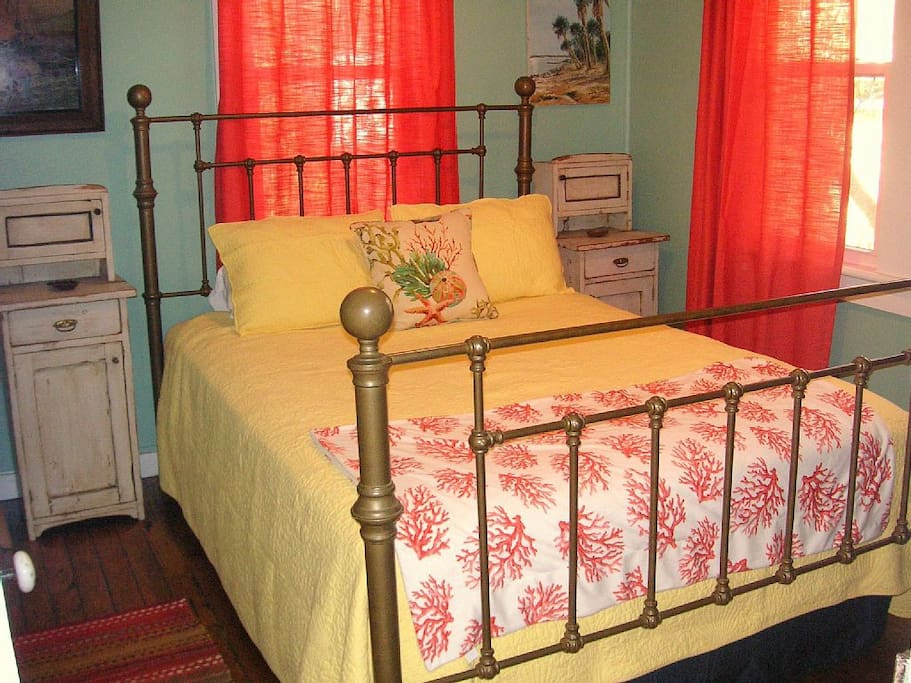 Romantic brass bed and gorgeous oversized stained glass window.
