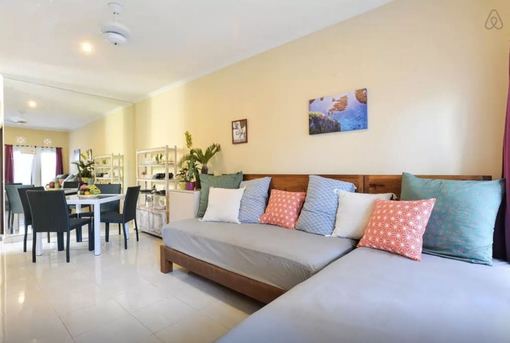 Shared living room: with 2 day-beds/sofa, dinning table for 4, airflow from small indoor patio and windows (mosquito proof) and ceiling fan + dinning table for 4 people. Dining table with chairs fits 4 people (not 6) to keep the living area spacious. Plat