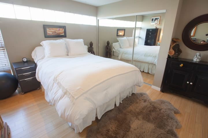 Guest Bedroom with SUPER comfortable queen bed - feather bedding throughout, and large TV mounted on wall