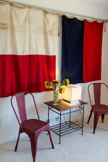 A pair of Navy Signal Flags cover a large wall with seating for a drink, early morning coffee or midday energy bar.