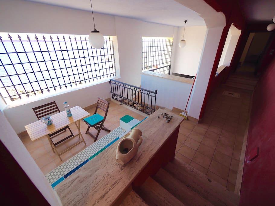 Dette arealet hører med til leiligheten, hyggelig spiseplass med oppmurt sofa 5 meter fra havet.
