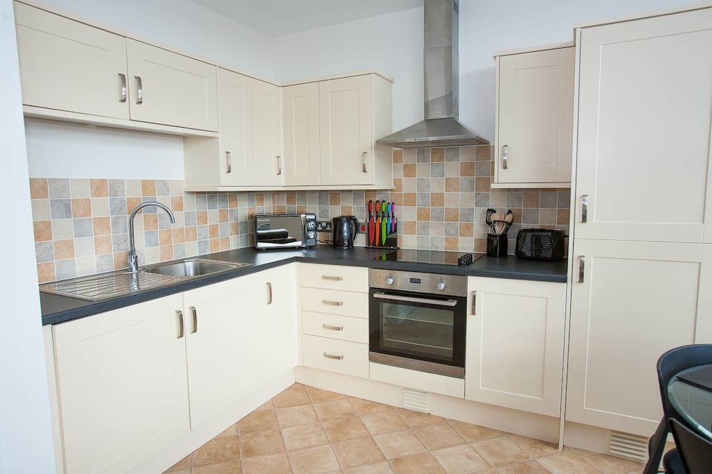 Kitchen Spacious kitchen with several cupboards, washing machine, microwave, fridge/freezer, kettle, crockery, cutlery, chopping knives and board, cooking utensils, saucepans, frying pan, oven trays, scissors, tea and coffee welcome pack, distant views of the countryside
