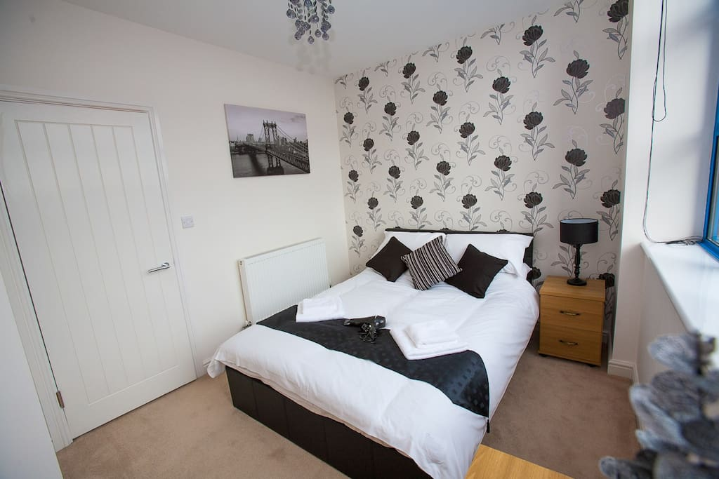 Beautifully decorated double bedroom with chest of drawers, bedside cabinets, wardrobe and hairdryer.