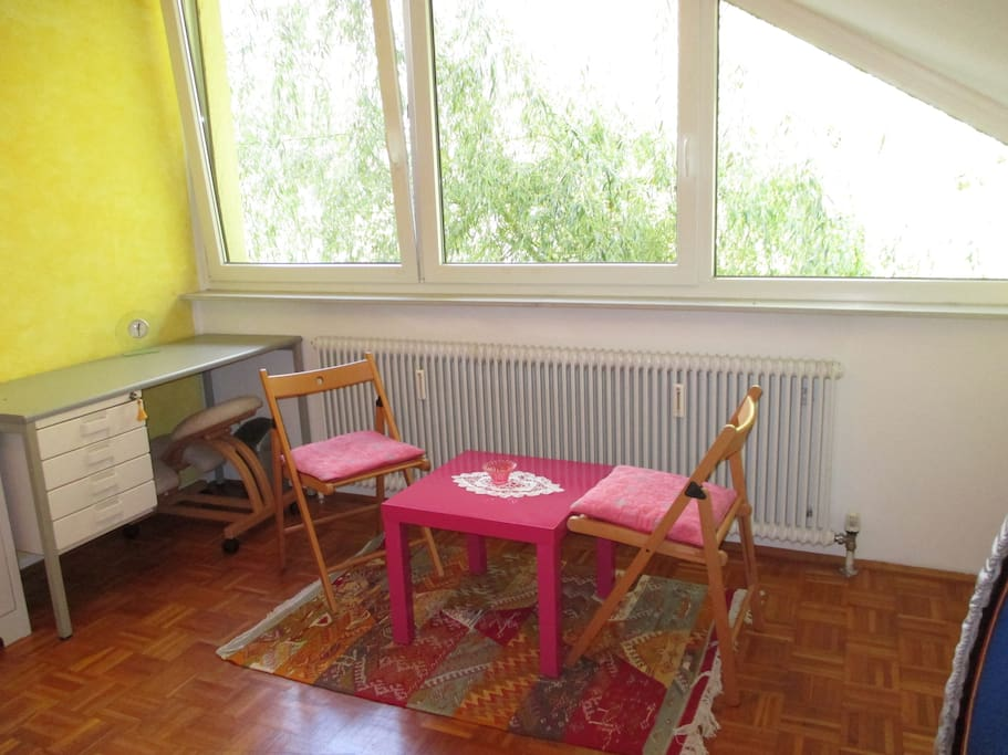 desk, coffee table and chairs in front of the window with willow outside