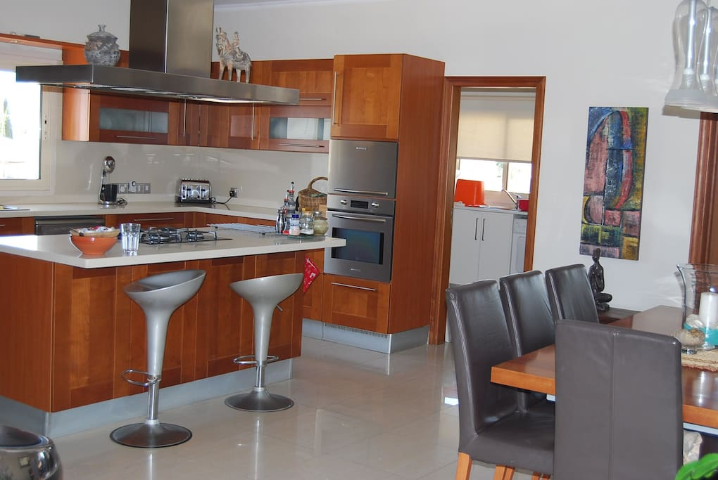 Open plan kitchen with central island and large dining table
