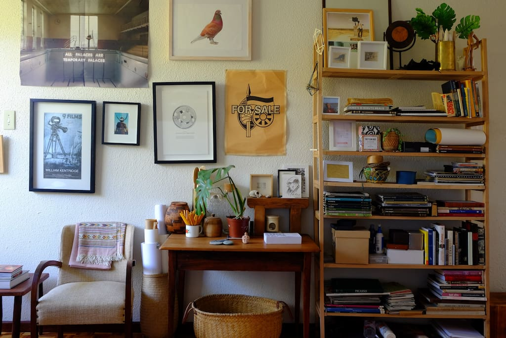 Art and our bookshelf, crowded with treasures and books from around the world.