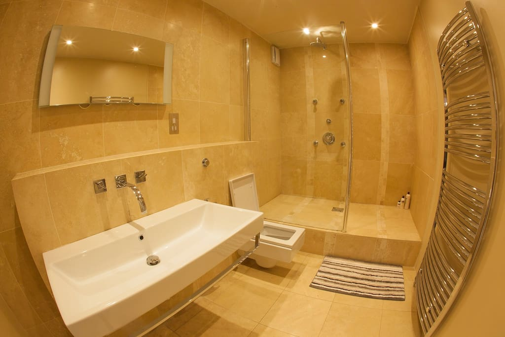 Hotel-style bathroom with rain shower, body jets, double sink and towel rail.