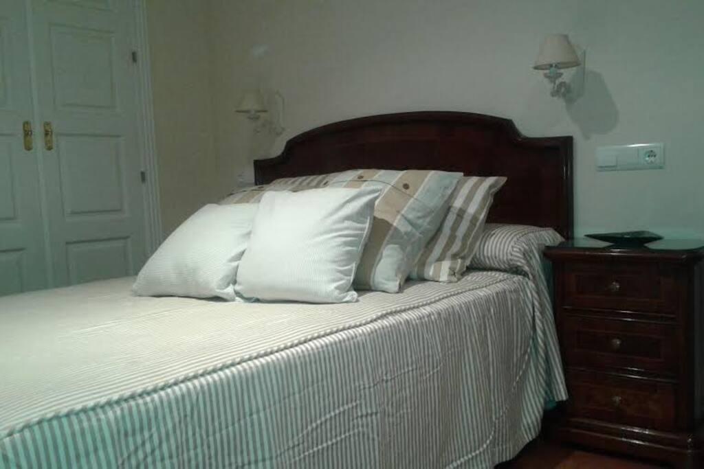 Dormitorio de matrimonio con cama de 1,50, armario y mesa de trabajo.