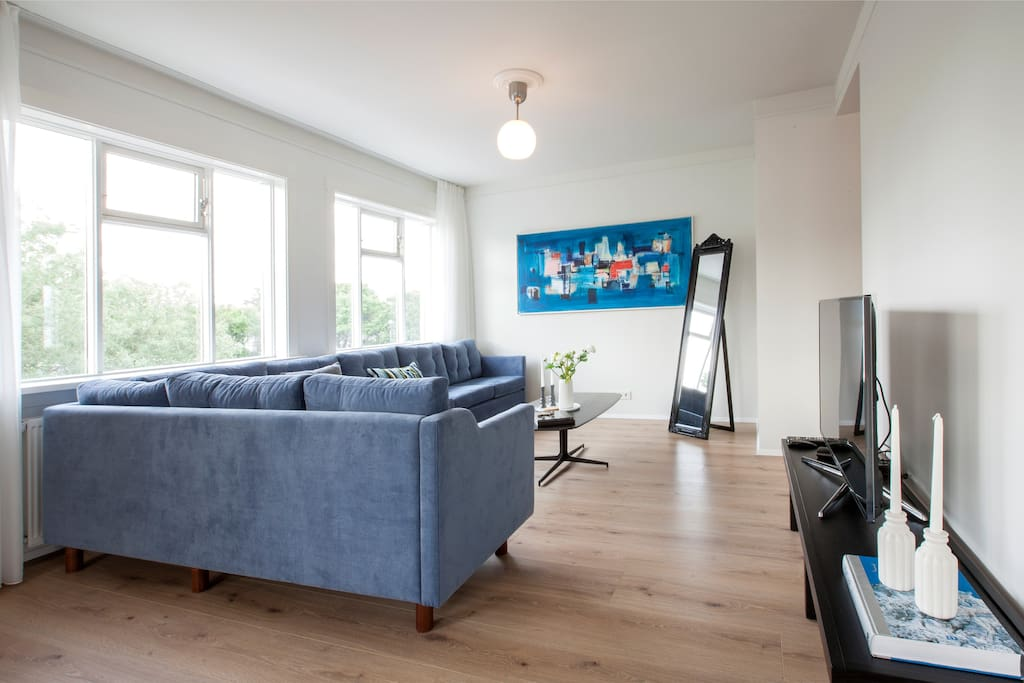 Modern and bright living rooms with  comfortable, large sofas and a big flat screen TV