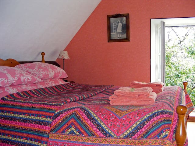 The guest bedroom has a comfortable king-size bed and a pleasant rural view