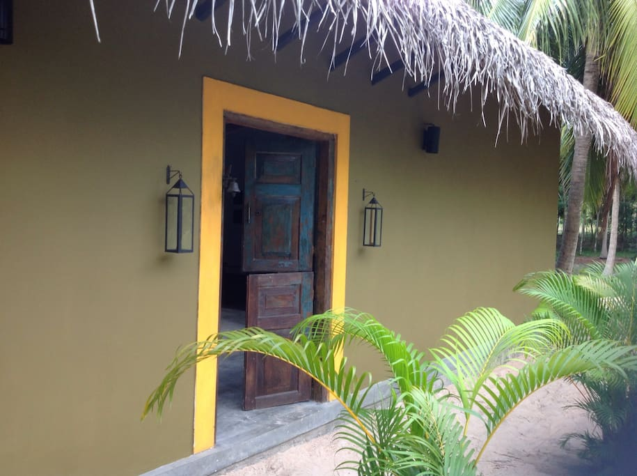 The entrance to the villa.Traditional antique door and cadjan roof.Typical srilankan style design.