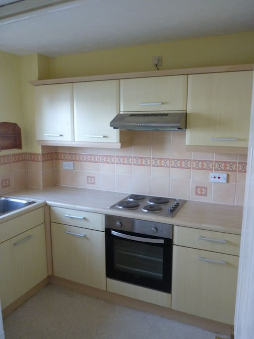 Kitchen with oven, fridge freezer, washing machine/dryer and microwave.