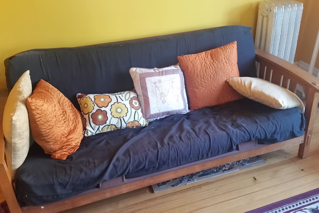 Futon pulls flat into full size bed, comfortably fitting two.