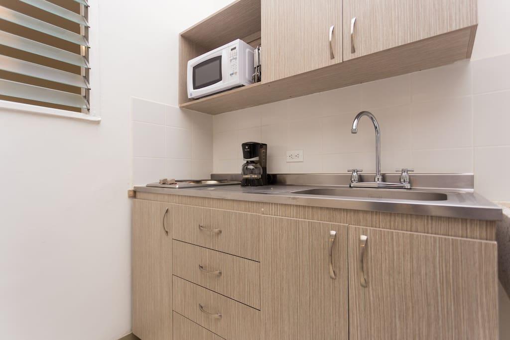 Cocina integral con utensilios y microondas. Kitchen with microwave