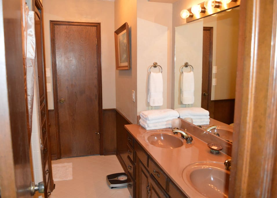 Your bathroom with tub-shower combo and twin sinks.