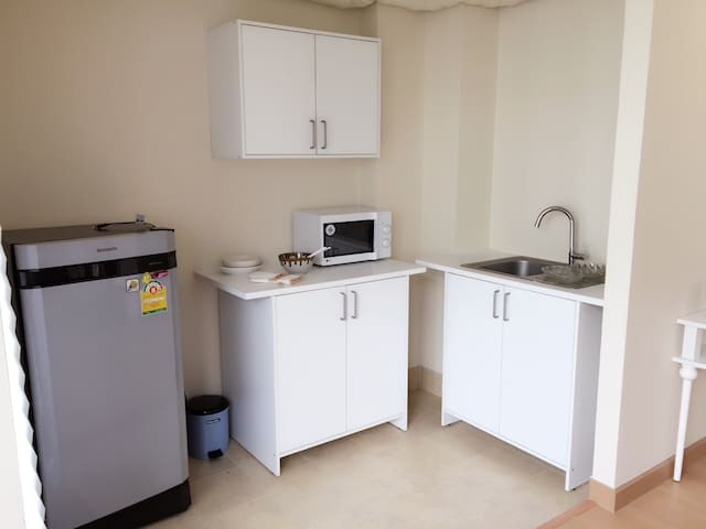 Functioned kitchen with sink, microwave, fridge, plus utensils...
