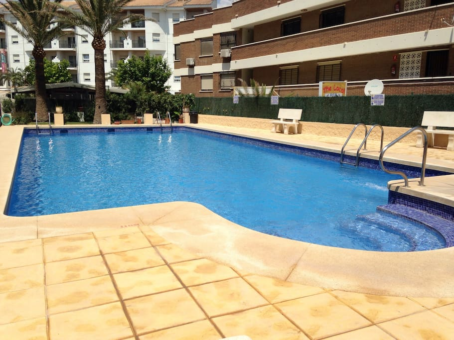 Pool area at the rear of apartment with parking and two minute walk to town !
